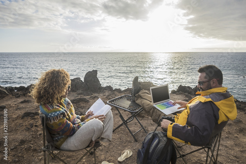 couple of alternative traveler sitting on the rocks in front of the ocean and the sunset enjoying the freedom and working with a laptop or reading a book Wallpaper Mural