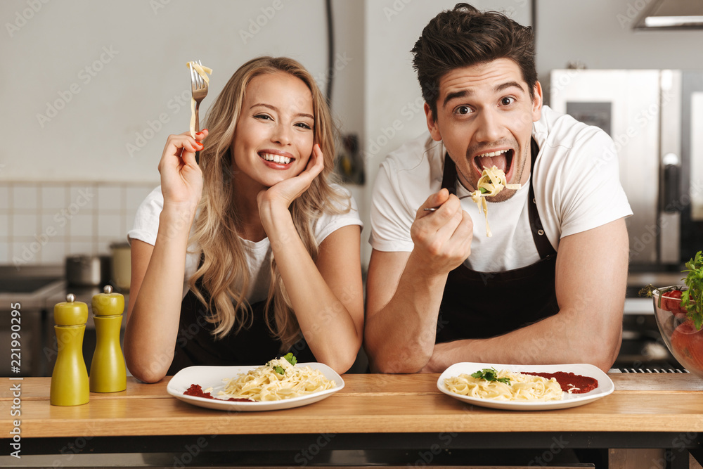 Fototapeta Emotional excited young friends loving couple chefs on the kitchen eat tasty pasta.