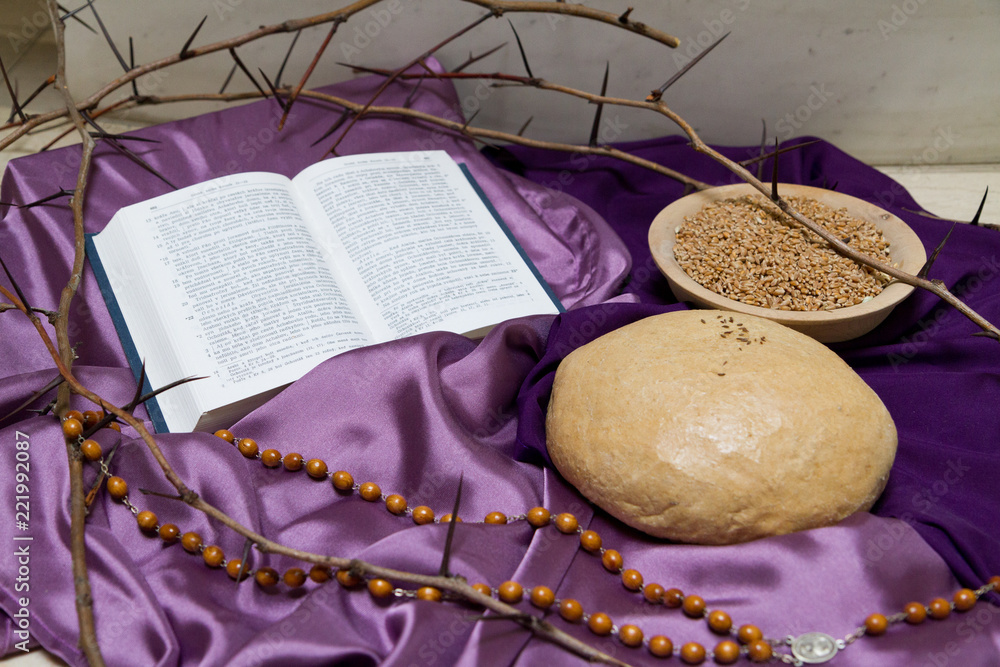 Bratislava, Slovakia. 2018/3/18. An open Bible, bread, rosary and crown of thorns as a thematic decoration in front of the altar during Lent in the Church of Queen of Family on Teplicka street.
