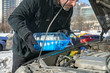 Man filling a windshield washer tank of a car by antifreeze on busy Moscow street in winter