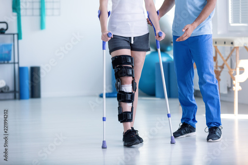 Fotografia Sport physiotherapist and patient with leg injury during training with crutches