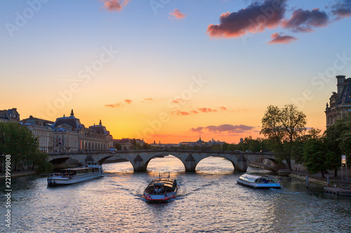 Leinwand Poster Beautiful vibrant sunset over the river Seine in Paris, France, with a tourist c
