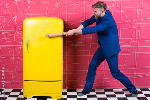 Photo  Man formal elegant suit beat with wooden bat retro vintage yellow refrigerator