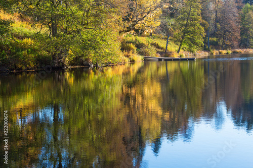 Beach with a jetty and autumn colors reflecting in the water
