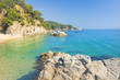 Marine tropical lagoon. Turquoise water on beach with white sand and rocks along coastline. Beaches of Lloret de Mar, Costa Brava, Spain. Clear summer day at sea. Nature of Mediterranean.