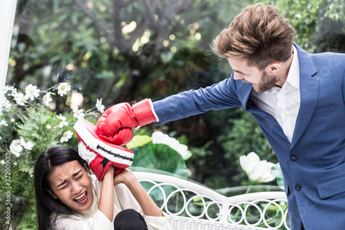 Business man and woman fighting with boxing gloves,Hit on