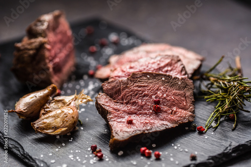 Juicy beef steak with spices and herbs on wooden cutting board