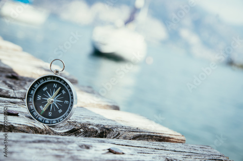 Fotografia, Obraz Kompass auf Holzplanken eines Steges, Boot im Hintergrund, Business