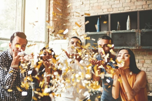 Obraz Party fun. Group of beautiful young people throwing colorful confetti and looking happy. - fototapety do salonu