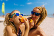 Mom and daughters eat peaches on the beach by the sea