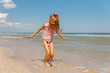 The girl jumps on the beach