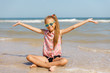 Portrait of a happy little girl with glasses on the beach