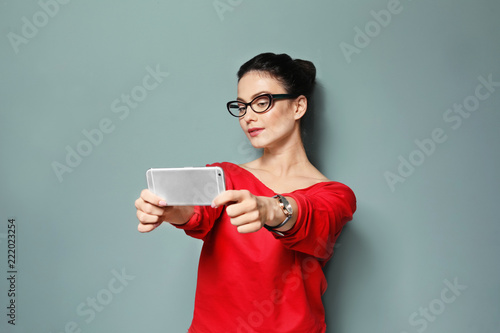 Photo Attractive young woman taking selfie on grey background