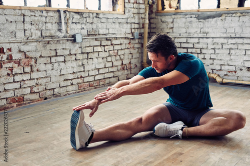 Fotografie, Obraz  Caucasian Man Stetches in Studio Before a Workout