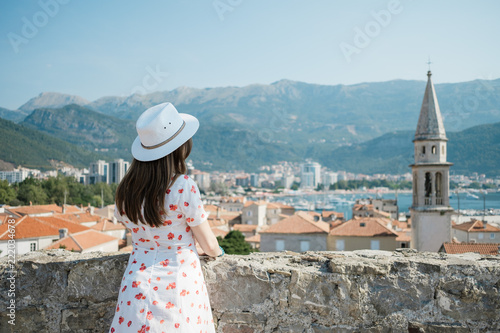 Fototapety, obrazy: Back view of a young beautiful woman holding her straw hat at the beach and looking to the horizon.