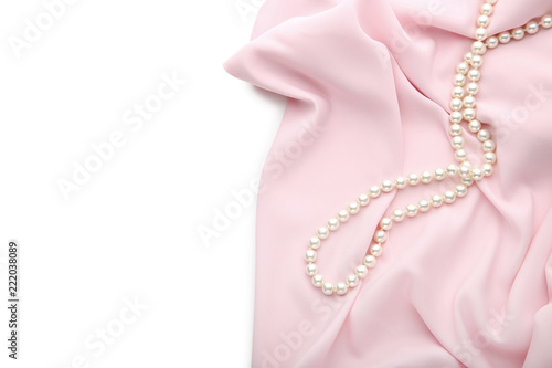 Pearl necklace with pink satin fabric on white background