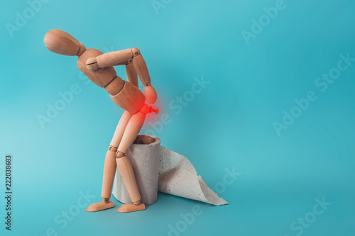 Photo Wooden figure sit on a roll of toilet paper