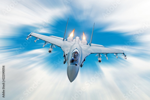 plakat Combat fighter jet on a military mission with weapons - rockets, bombs, weapons on wings, at high speed with fire afterburner engine nozzles, flies in clouds motion blur.