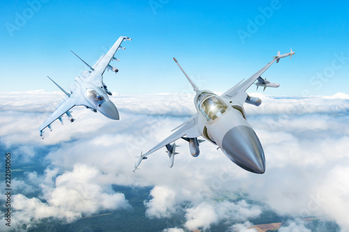 fototapeta na lodówkę Pair of combat fighter jet on a military mission with weapons - rockets, bombs, weapons on wings flies high in the sky above the clouds.