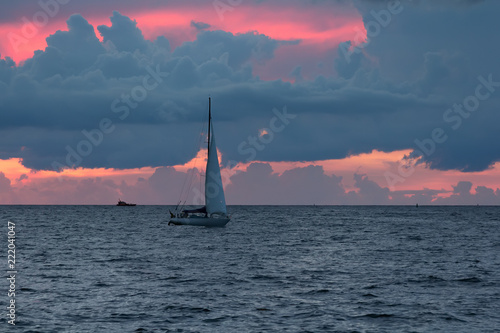 Pleasure boat is sailing to harbor to the Gulf of Riga after sunset