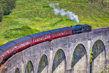 Close Shot Of Jacobite Train Travelling Over The Glenfinnan Viaduct With A Green Hillside Behind It And Steam Coming Out Of The Locomotive