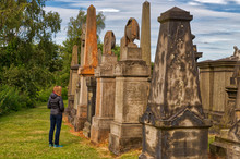Caucasian Woman In A Coat Looking At Large Gravestones During The Day In A Green Cemetery In Scotland