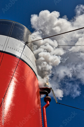 Stampa su Tela Closeup of a steamboat whistle blowing out white steam from the stack and a clea
