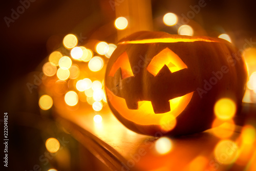 Foto op Canvas Herfst A cheerful smiling Jack O Lantern on halloween placed on a fireplace with fairy lights