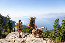 Man, Woman And Dog Are Hiking During A Vibrant Summer Sunset. Taken In Howe Sound, Near Vancouver, BC, Canada.