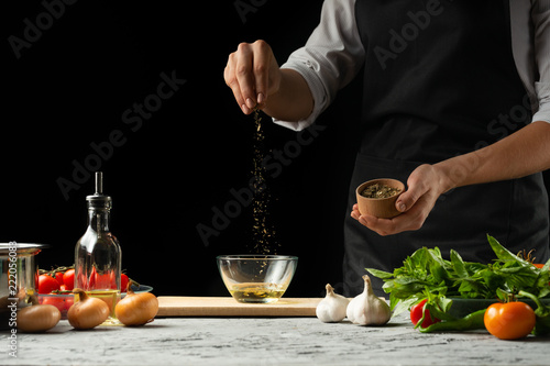 Preparation of tomato sauce by the hands of the chef, steps the process in the kitchen on a black background copy the text of the recipe.The concept of cooking food