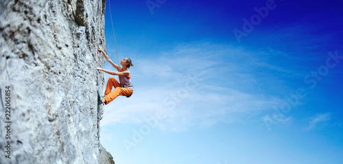 Photographie young slim woman rock climber climbing on the cliff
