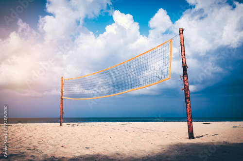 Volleyball court on an empty beach with blue cloudy sky.