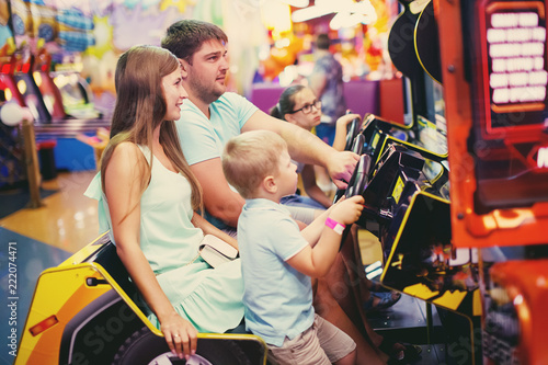 Cute girl plays a rifle shoots arcade in game machine at an amusement park Fototapete
