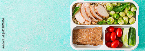 Healthy green meal prep containers with chicken fillet, rice, brussels sprouts and vegetables overhead shot with copy space. Dinner in lunch box. Banner. Top view. Flat lay