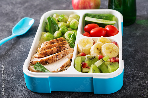 Healthy green meal prep containers with chicken fillet, rice, brussels sprouts, vegetables and fruits overhead shot with copy space. Dinner in lunch box.