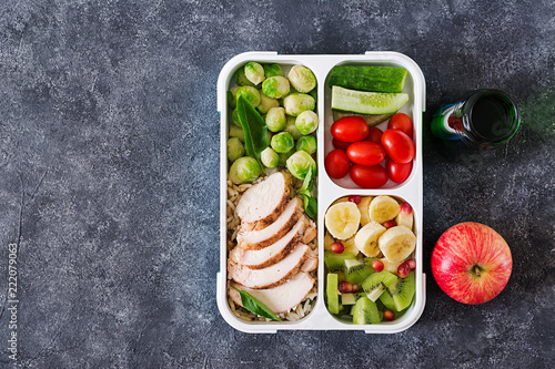 Healthy green meal prep containers with chicken fillet, rice, brussels sprouts, vegetables and fruits overhead shot with copy space. Dinner in lunch box. Top view. Flat lay