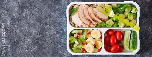 Healthy green meal prep containers with chicken fillet, rice, brussels sprouts, vegetables and fruits overhead shot with copy space. Dinner in lunch box. Top view. Banner. Flat lay