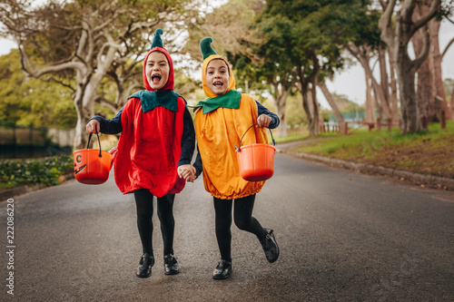 Fotografering Cute little girls trick or treating in halloween costume