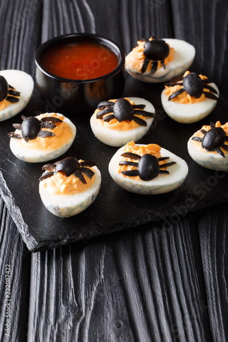 deviled eggs stuffed with mustard and yolk decorated with olive spiders close-up served with ketchup. vertical