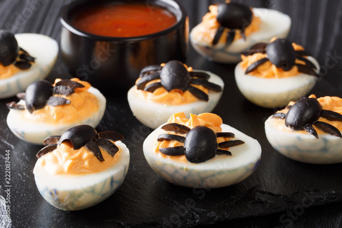 Halloween appetizer deviled eggs stuffed with mustard and decorated with olive spiders and cobweb close-up. horizontal