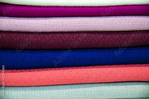 Tuinposter Stof A multicolored stack of fabrics - the fabrics lie on top of each other