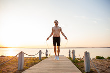 Portrait Of Muscular Young Man Exercising With Jumping Rope