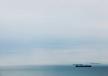 Cargo Ships Anchored On A Still Sea In A Stormy Bay