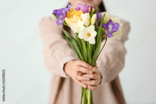 Fotografía Little girl with bouquet of flowers on light background