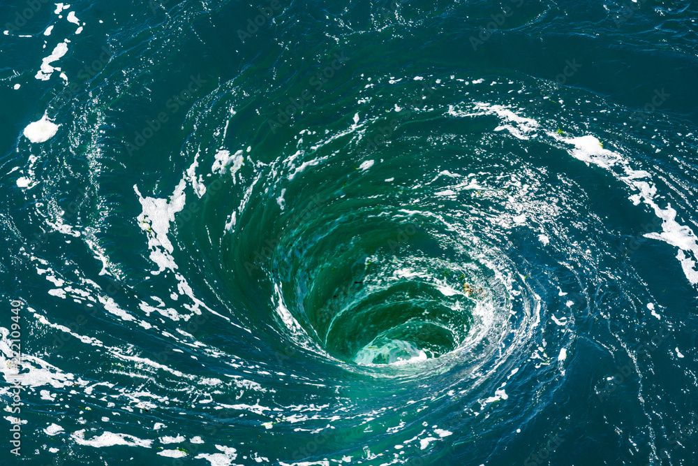 Fototapeta A powerful whirlpool is generated at the surface of the green waters of the river Rance by the action of a turbine of the tidal power station near Saint-Malo in Brittany, France.