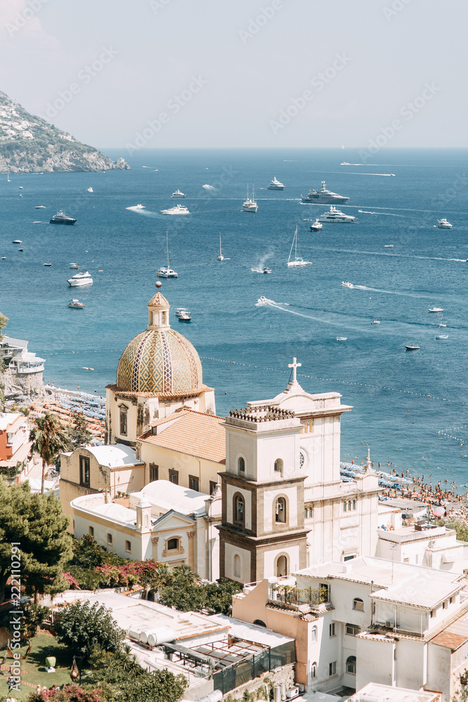 The coast of Positano, Amalfi in Italy. Panorama of the evening city and the streets with shops and cafes. Houses by the sea and the beach. Ancient architecture and temples