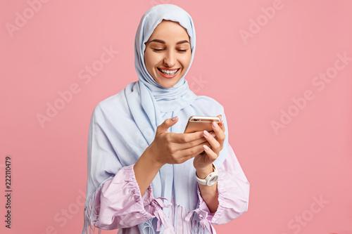 Slika na platnu Happy arab woman in hijab with mobile phone