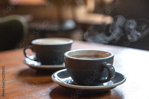 Photo sur Aluminium Cafe Closeup image of two blue cups of hot coffee on vintage wooden table in cafe