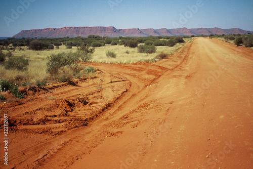 Fotografering  Una strada nel deserto australiano con rocce rosse sullo sfondo - Mereenie Loop