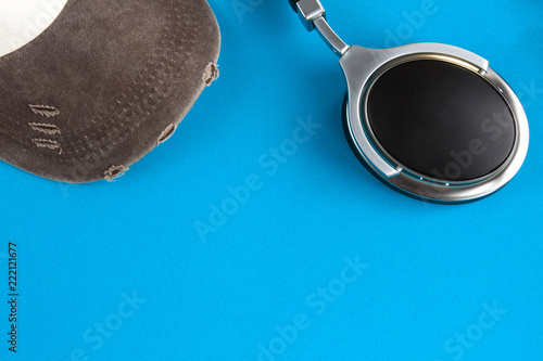 Fotografia  Baseball cap in the left corner and headphones in the right corner on a blue bac